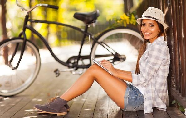 Picture girl, nature, bike, smile, the fence, shorts, brunette, laptop, shirt