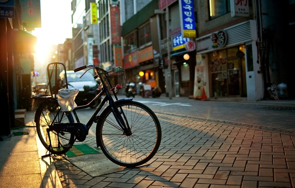 Picture the sun, rays, bike, the city, street, road, home, morning, signs, the sidewalk, stores, funiture