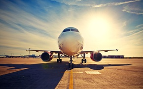 Picture the sky, asphalt, the sun, the plane, shadow, airport, runway, passenger, terminal