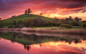 Picture the sky, grass, water, trees, sunset, reflection, river, hill, houses