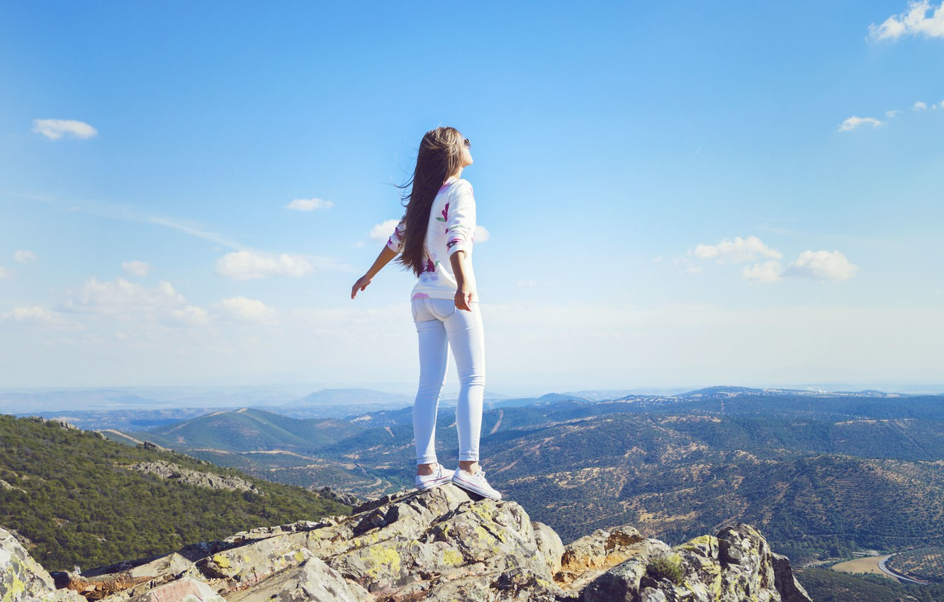 Photo wallpaper the sky, girl, clouds, pose, the wind, hair, mountain, jeans, horizon, is